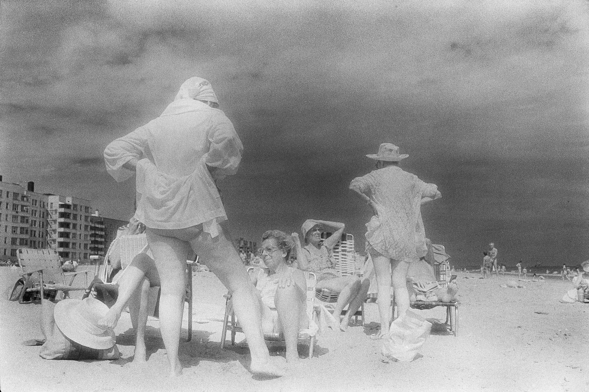 Barbara Alper- Photo of family talking and relaxing on Rockaway Beach NYC