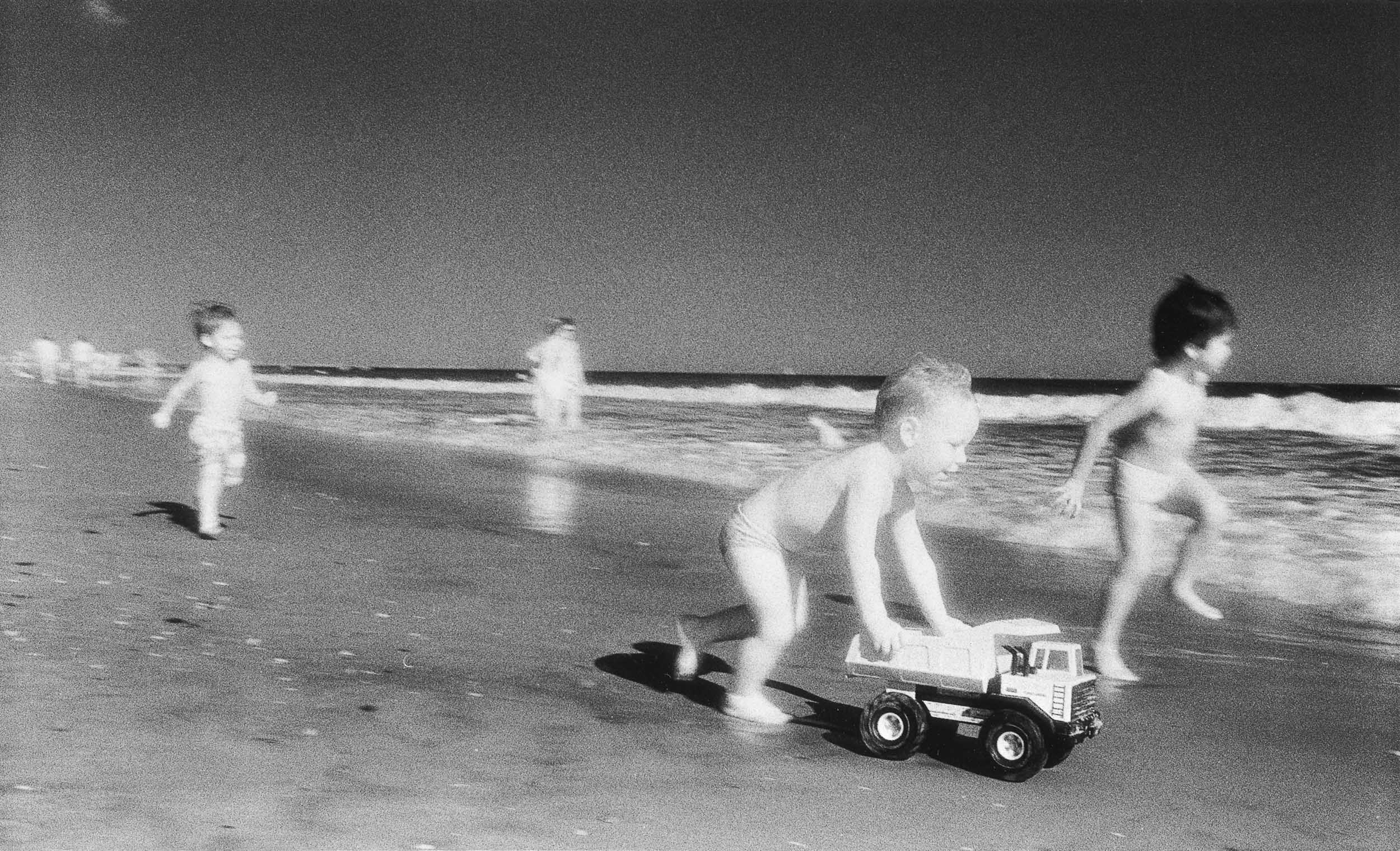Barbara Alper- Photo of young boys playing with a toy truck on Rockaway Beach NYC