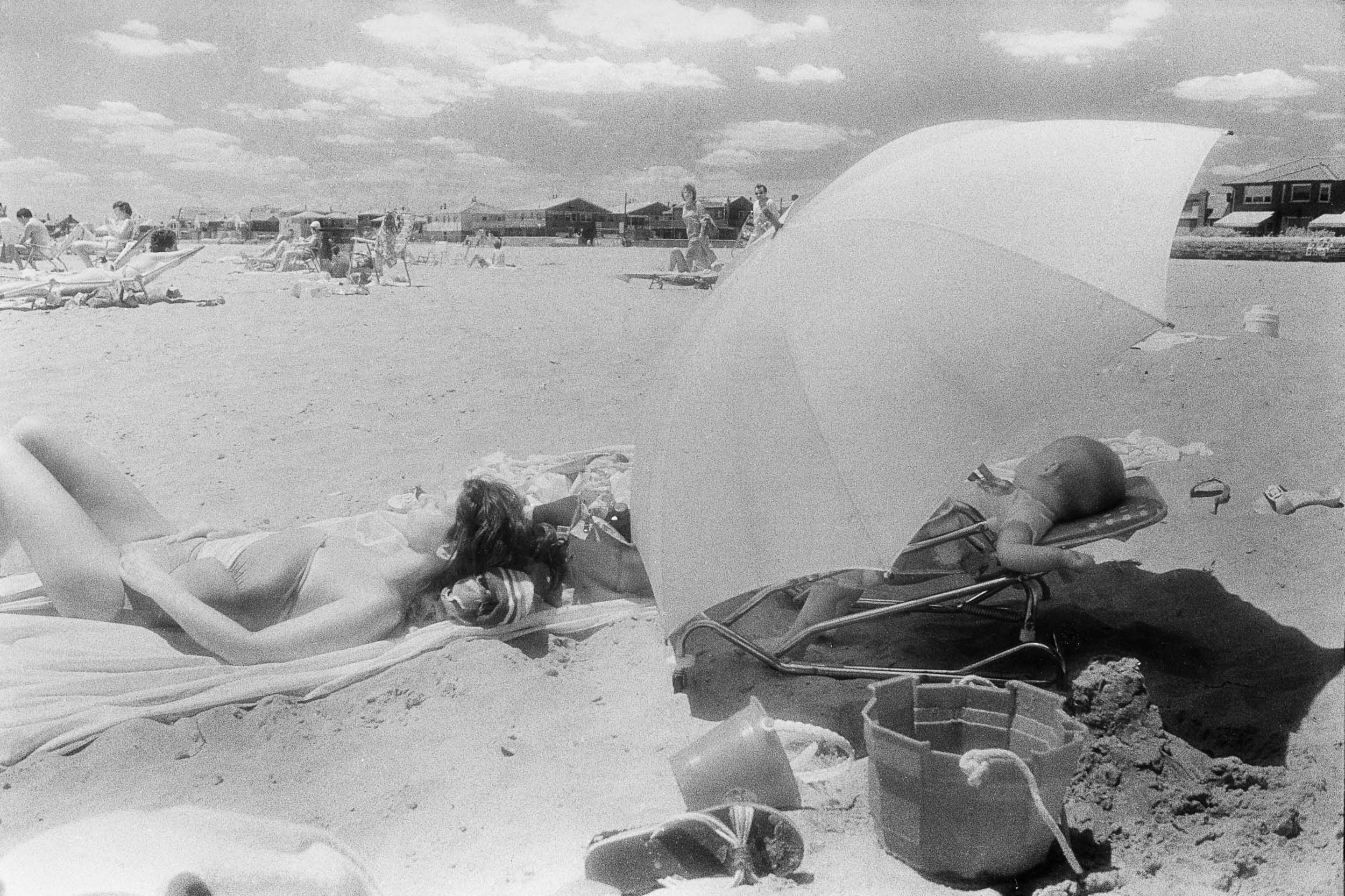 Barbara Alper- Photo of women and baby sleeping under umbrella at Rockaway Beach NYC