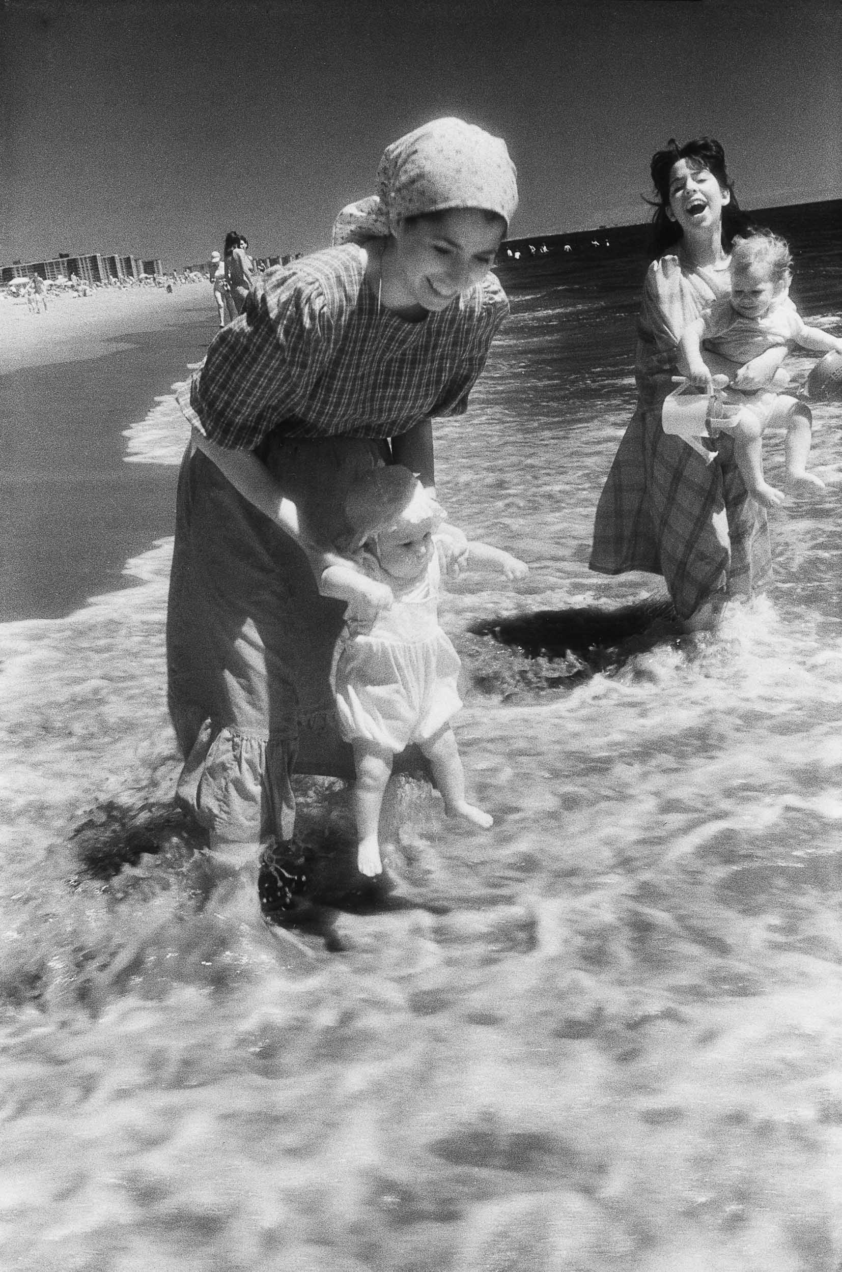 Barbara Alper- Photo of orthodox women holding babies in the water at Rockaway Beach NYC