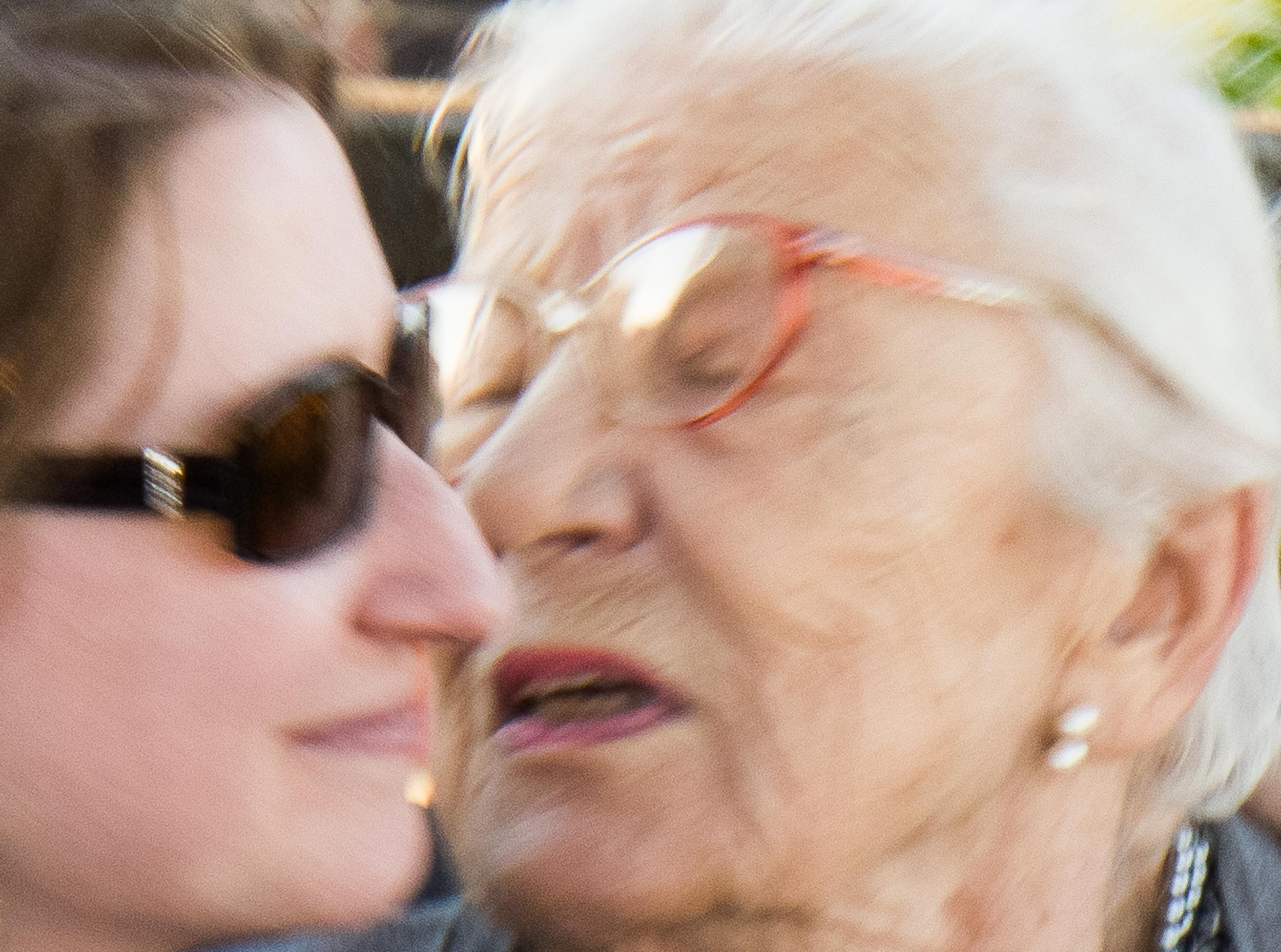 Barbara Alper- Photo of two women greeting, one younger and one elder, faces  together, emotional, in motion, closeup