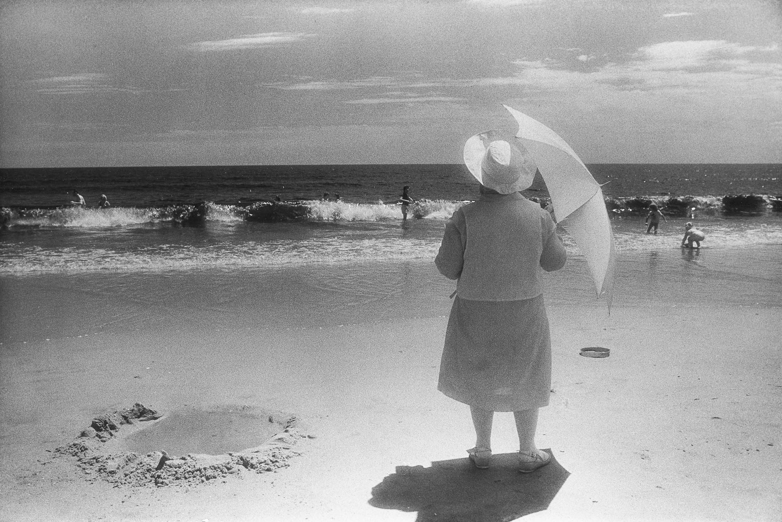 Barbara Alper- Photo of women holding an umbrella while watching the waves at Rockaway Beach NYC