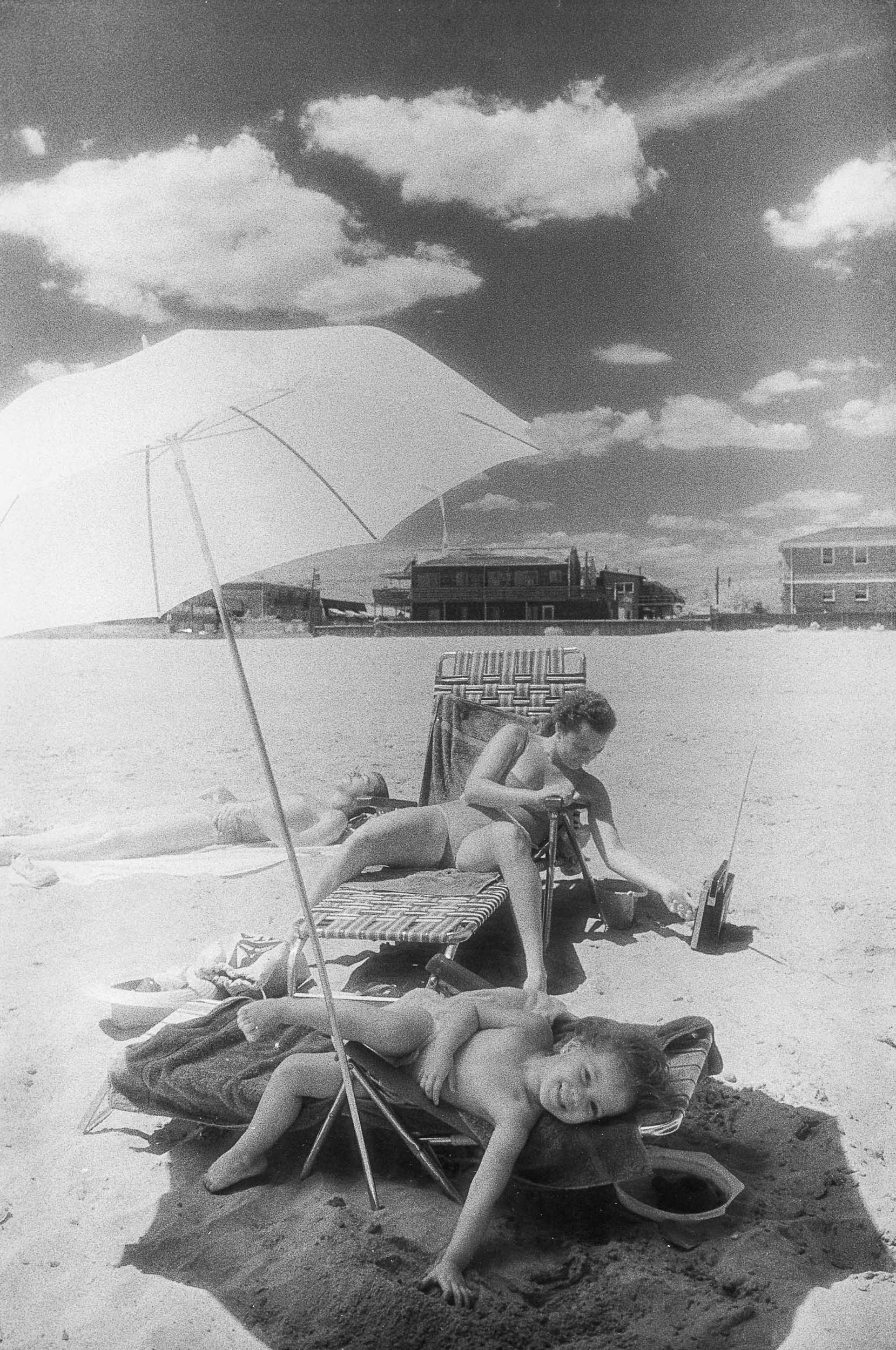 Barbara Alper- Photo of a child lyingunier umbrella  with his mom on Rockaway Beach NYC