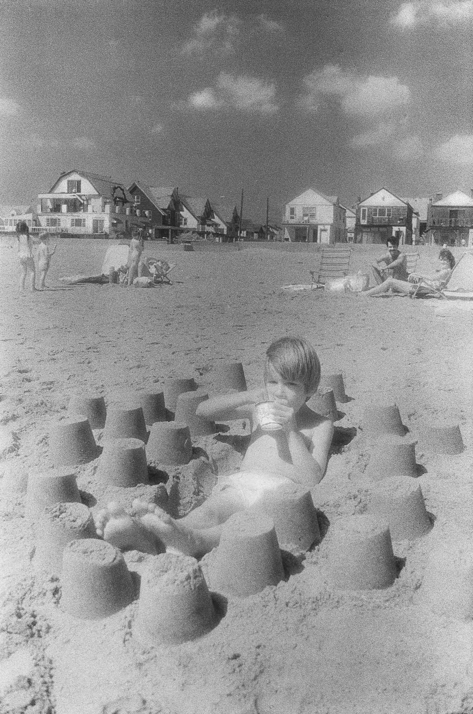 Barbara Alper- Photo of a boy building sand castle at Rockaway Beach NYC