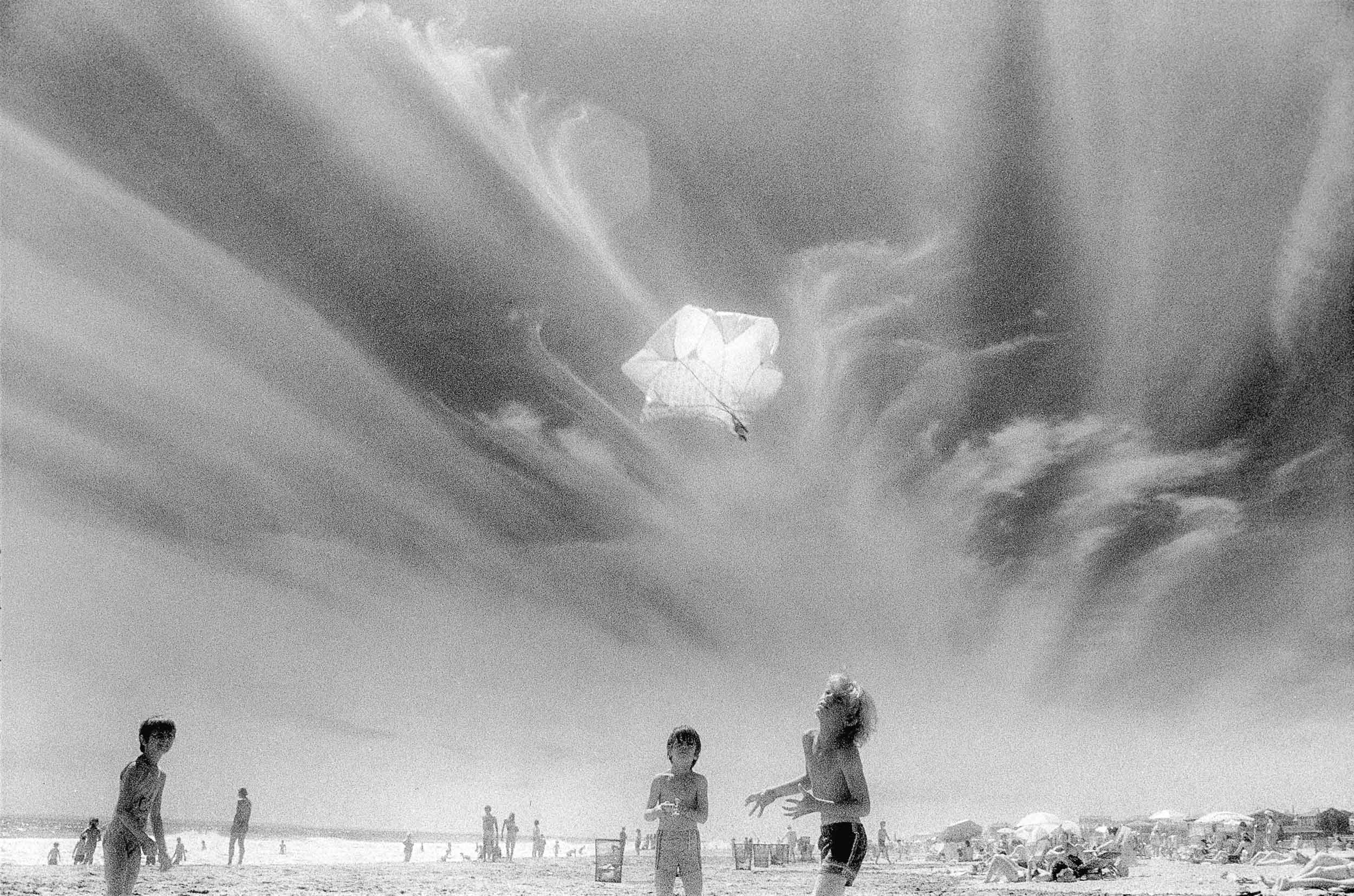 Barbara Alper- Photo of kids tossing up a toy parachute into clouds at Rockaway Beach NYC