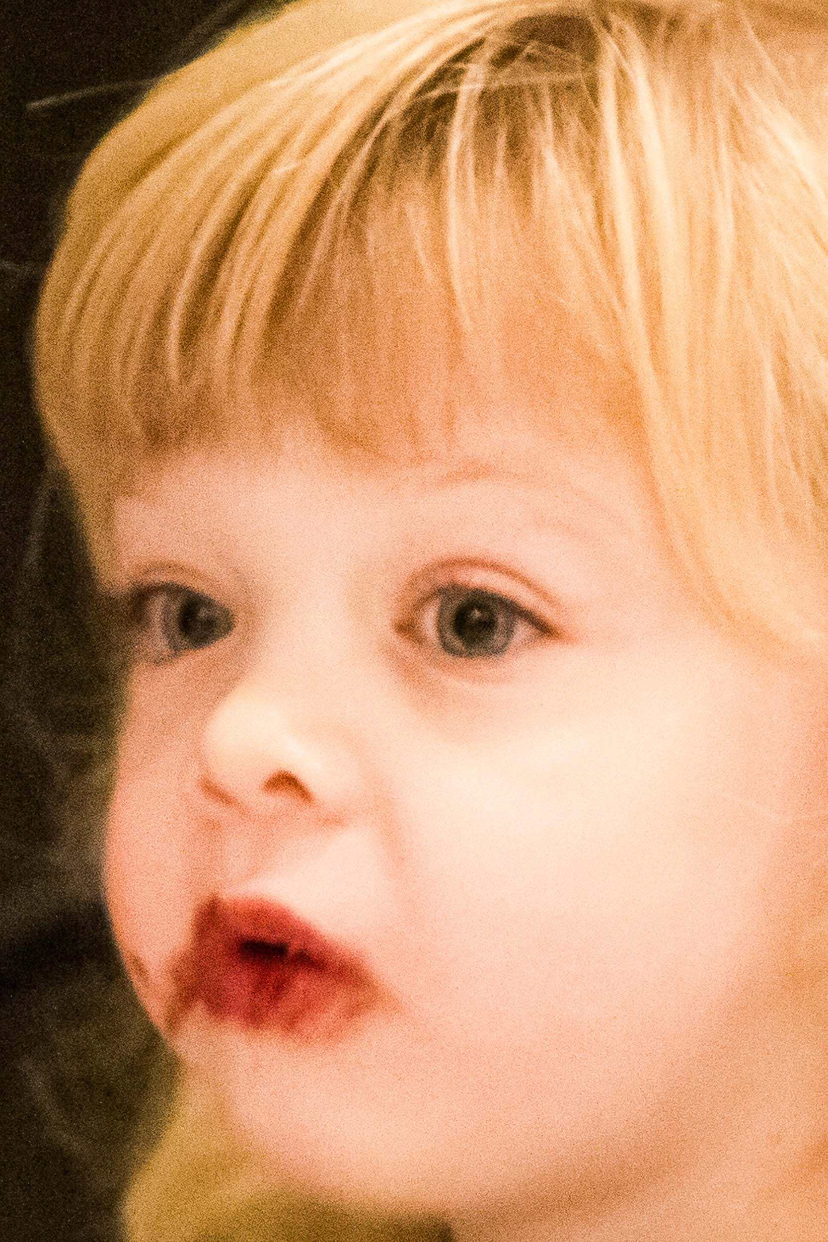 Barbara Alper- Photo of a young blond girl, with round cheeks, red lips and food around her mouth, closeup