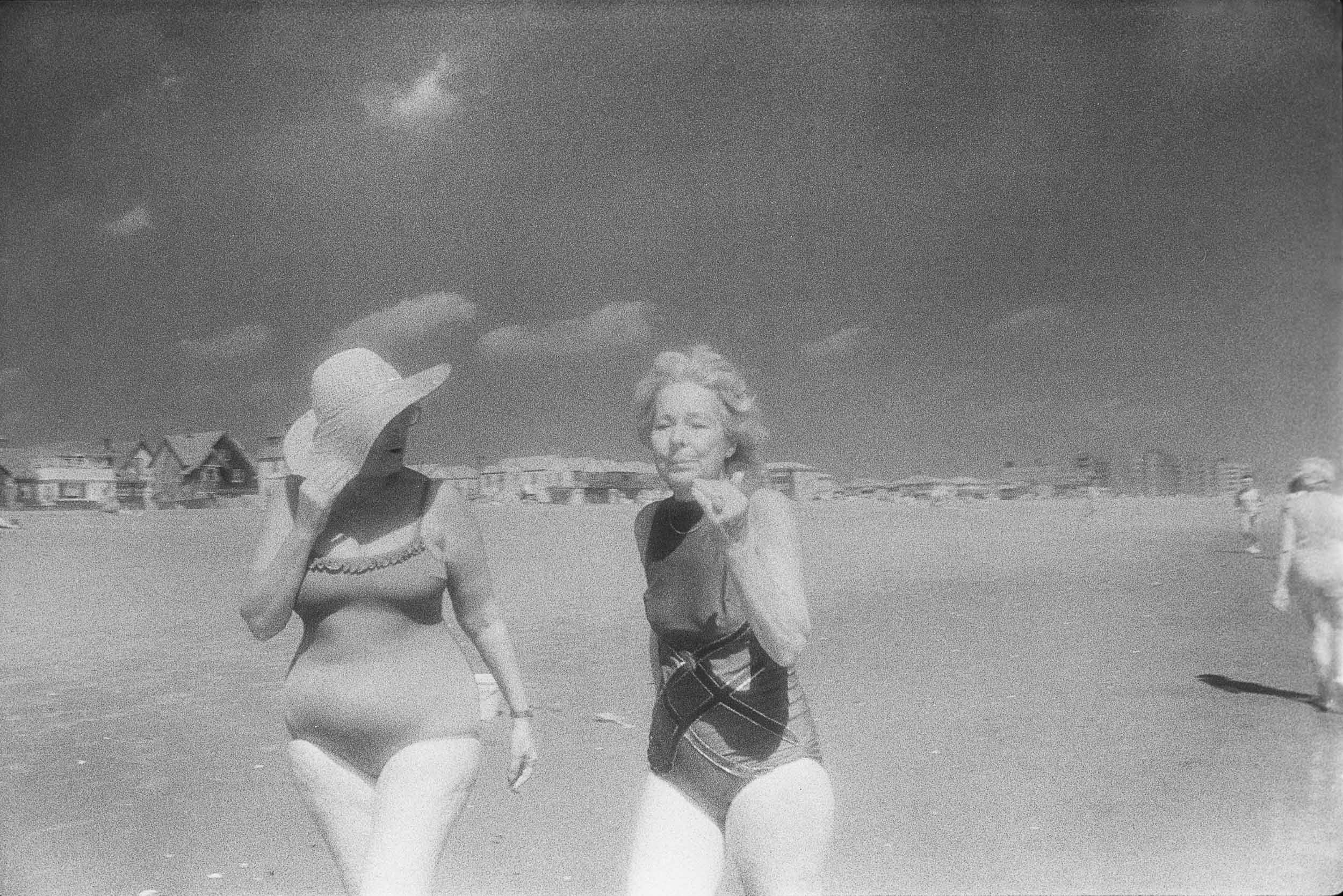 Barbara Alper- Photo of women walking and talking together on Rockaway Beach NYC